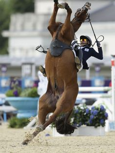 Hwang Woojin, of South Korea, and his horse Shearwater Oscar, fall down after the horse bucked after the starting bell sounded to start their run in the equestrian show jumping stage of the men's modern pentathlon at the 2012 Summer Olympics, Saturday, Aug. 11, 2012, in London.(AP Photo/Markus Schreiber)