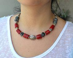 Un collier de corail rouge de haute qualité, conçu avec des grosses perles de corail naturel, jaspe naturel des taches noires et intercalaires en argent vieillis et perles, une breloque petit navire pend au bout du collier.  Absolument magnifique collier de couleur rouge qui peut être porté en toute occasion.  Longueur: 18» (46cm), perles de corail: 13x17mm ca.  Corail a été appelé le «jardin de la mer». Il était censé prévenir fortune malade et offrent une protection contre la maladie…