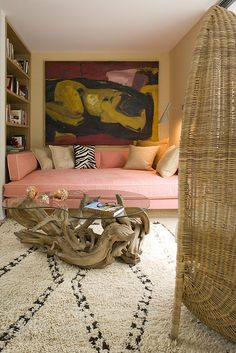 Wow! This is a wild room. What's really interesting is that it feels like the woman in the big painting could curl up on the giant sofa. Yes, the pink sofa picks up the patch of pink in the painting, but there is so much more going in the sofa-art relationship.