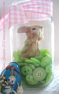"""Hello there! Today I am bringing you a super simple tablescapeidea for spring using buttons, ribbon and clear glass jars…a """"button-scape"""" if you will! I'm willing to bet we all have a hodgepodgeof glass containers around the house (mason jars are one of my favorites) along with small spring and Easter themed nic-nacs. Why not … … Continue reading →"""