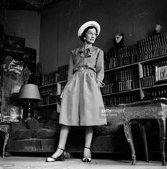 Coco Chanel. Paris-1950- Coco CHANEL, styliste fran?aise de la haute couture, posant en attitude, v?tue d'une 'robe culotte' avec une encolure orn?e d'un noeud, ceintur?e, mains dans les poches, coiff?e d'un chapeau, dans le salon de son appartement rue Cambon.