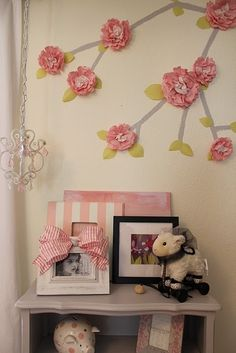 paper flowers on wall super cute for a baby girls room @terra let me know if you want some! ;)
