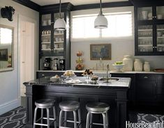 Black and white is a timeless look, particularly in the kitchen. The owner of this kitchen in San Francisco wanted designer Stephen Shubel to reflect her personal style: classic with an edgy streak. The black cabinets feel ageless, and the silver swivel stools add a little bit of flair. A white backsplash, countertop, wall, and accents keep the space airy.