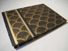 *Description* This hardback book, ideal for use as a guest book or photo album, is covered with black and gold art deco paper. The end paper is black. This book is coptic bound to open completely flat and is sewn with black linen bookbinding thread. All books are hand bound, from