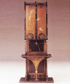 * Carlo Bugatti, Italian (1856–1940) Walnut cabinet with ebonized wood, hammered copper inlaided pewter and calligraphy. H. 7', W. 3'. Bugatti was a notable decorator, architect, designer and manufacturer of Art Nouveau furniture, models of jewelry and musical instruments. He was also the older brother of Ettore, designer of the Bugatti automobile.