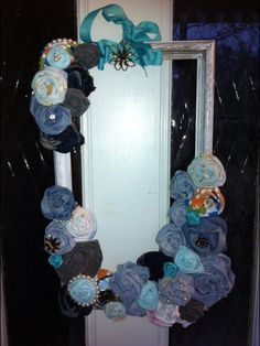 Shabby Chic Door Hanging Wreath by Stacy Webb. Cost $0 since I made from things around my home. Wasn't sure what to hand on my front door after the Christmas stuff, so came up with my own Jan./winter look. I used: -I broke a piece of garage sale art. -Whitewashed the frame. -Made fabric flowers out of my daughter's old jeans and pajamas. -Embellished with my broken jewelry. -Ribbon