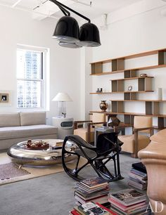 Reed Krakoff's Inspiring New York City Office. Above a Laarman rocking chair is a light fixture by Ronan and Erwan Bouroullec; the shelving unit is a 1950s piece by Charlotte Perriand and Jean Prouvé.