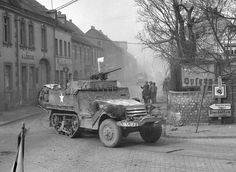 M3A1 half-track armored vehicle belonging to the 9th U.S. Armored Division in the streets Engers Germany, March 27, 1945. Note the Ma Deuce heavy machine gun on the half truck.