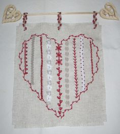 IDEA! Machine embroidery idea, image only. We can use embroidery designs on wall hanging projects. I love the wooden heart rod they used.
