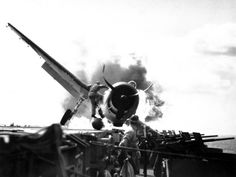 Crash landing of an F6F Hellcat into the port side of the USS Enterprise, November 10, 1943. Lieutenant Walter L. Chewning, Jr., USNR, the Catapult Officer, is climbing up the plane's side to assist the pilot from the burning aircraft. The pilot, Ensign Byron M. Johnson, escaped without significant injury. Note the plane's ruptured belly fuel tank.