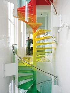 "A striking multihued spiral staircase is visible from nearly everywhere within this transparent house in west London. ""The staircase is the hub, the soul of the project,"" says the designer. ""It's meant to be enjoyed."" From the ground, the steps start with the cool colors of the earth, then get warmer as they reach up to the sky."