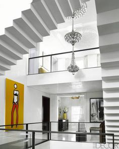 A painting by Julian Opie and a sculpture by Sol LeWitt in the entry; the Venetian plaster–clad staircase rises to the top floor, and the hanging light fixture is custom.