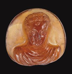 A ROMAN GARNET CAMEO   CIRCA 2ND CENTURY A.D.   Sculpted in high relief with a facing draped bust of a man, the eyes with heavy lids, his hair in two rows of tight curls, three small locks falling on to his forehead  11/16 in. (1.7 cm.) long