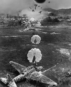 Parachute bombs about to land and explode on a Japanese plane camouflaged with branches and covered in graffiti on the ground during a lowlevel...