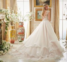 Morilee   Madeline Gardner Fairytale Wedding Dress in Blush. The ultimate princess ball gown with a full ruffled and tiered organza skirt and embroidered bodice with beading on illusion sleeves. This bridal gown features a plunging neckline and illusion back. Style 2895, also available in white and ivory.