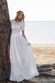 """Don't let the effortless vibes fool you, these gowns are far from """"casual.""""  Sure, the gauzy lace pieces look perfectly at home next to nature, catching a sea breeze while posed next to a majestic steed, but their intricate details and impeccable construction maintain a special elevation."""
