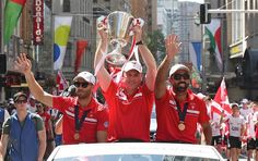 Coach John Longmire with Adam Goodes and Jarrad McVeigh with the AFL cup during the parade in Sydney today.