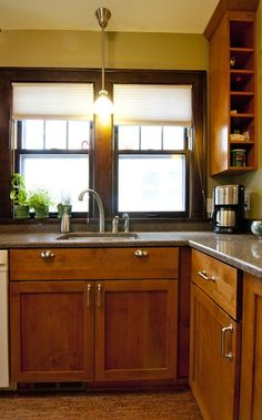 Contemporary Kitchen: Designed by castle Building and Remodeling. The cherry cabinets, cork flooring, and quartz countertops complete the design. The blend of the original woodwork around the windows and doors tie today's design with the character of yesterday.