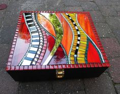 Elegant, decorative black wooden box covered with hand cutted stained glass, mirror, glazed ceramic tiles and glass tiles in red, orange, yellow,