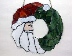 Stained Glass Santa Claus Christmas Wreath is sure to become a treasured family heirloom.  Approx.13 Diameter and ready to hang with hanging chain