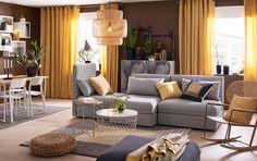 Mellomstor stue med 3-seters sofakombinasjon i ensfarget grått og mønster i svart og beige, som kan gjøres om til seng. Kombinert med et hvitt bord med oppbevaring og en moderne gyngestol i håndflettet rotting.