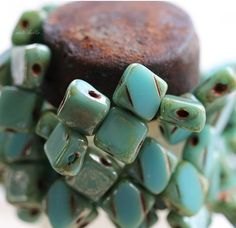 ✿Please read my shop announcement for upcoming shipping days, thank you!!!✿   Turquoise blue glass with a raised stripe on 1 side and metallic Picasso finish. The 2 holes run on the diagonal creating a diamond shape pattern. Turquoise Squares.....  Q u a n t i t y :: 25 beads = 1 strand  S i z e :: approx. 6x3.5mm, {1/4 inch = 6.35 mm} H o l e . S i z e :: less than 1mm  C u t / s h a p e :: 2 holes as seen in pictures, Silky shape  F i n i s h :: Picasso, fire polished  O...