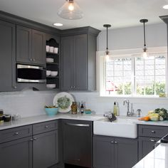 """This gorgeous Light French Gray SW 0055 kitchen has us waving our baguettes over our heads and saying """"Ooh, la la!"""" Paired with Dura Supreme cabinetry and a design by Gwen Adair of Cabinet Supreme by Adair, this kitchen achieves the perfect balance of sleek modern and warm rustic."""