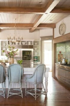 A stunning French and Gustavian inspired kitchen with wood ceiling, vintage rattan chairs at island, and aqua green accents. Decor de Provence.