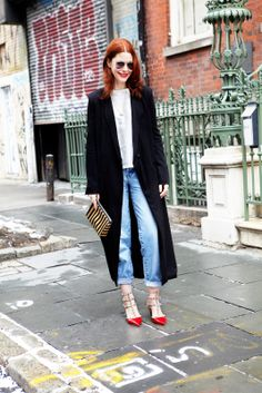 """What Our Editors Wore To NYFW #refinery29  http://www.refinery29.com/43013#slide25  """"This look is sort of a non-look...with the exception of the shoes. I really like the contrast between the severe long black coat and these whimsical red shoes. It's casual but still a little fierce."""" Vintage Lee jeans, Assembly New York duster coat, Mayle striped clutch, Valentino Rock Stud ankle-strap shoes ($945, available at Bergdorf Goodman)."""