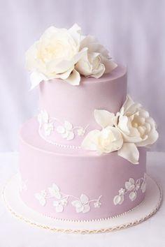 Torta de color lila decorada con flores de azúcar de color blanco. #TortaDeBodas