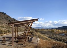 Picnic shelter designed with repurposed railroad steel tracks. Located on the Rio Grande Bike path along the Roaring Fork River, Colorado.  Land+Shelter www.landandshelter.com   info@landandshelter.com © Brent Moss Photography