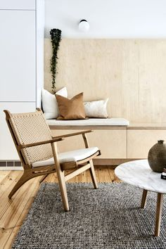 Warm wood tones picked out in the chair and built in plywood storage bench | Highett House — Bicker