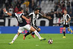 Daniel Alves (R) of Juventus FC is tackled by Gianni Munari of Cagliari Calcio during the Serie A match between Juventus FC and Cagliari Calcio at Juventus Stadium on September 21, 2016 in Turin, Italy.