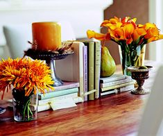 Sometimes the best decorations come from unexpected places. This Thanksgiving centerpiece is built on a foundation of books, whose bindings add color to the table. The stacks are surrounded by an assortment of mismatched vessels filled with fall colored blooms. Other seasonal accents -- such as the feathers and pear -- add visual interest to the vignette.