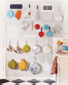 Genius kitchen DIY: Use a pegboard to make a pot-rack alternative. Keep the look streamlined by painting the board the same color as your walls.