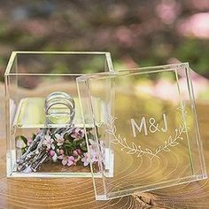 Give your own personal touch to your wedding ring box without overdoing it. This simple acrylic box gives you a chance to fill the bottom portion with whatever you'd like, whether little mementos, a picture, or pretty greenery. Both of your rings will sit nicely on top with a monogrammed cover to keep it all secure. | 11 Fun Ring Bearer Boxes, Pillows, and More
