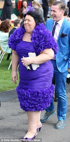 Having fun: A lady in an eye-catching purple ensemble giggles as she enjoys the sunshine at horse racing Oh dear............