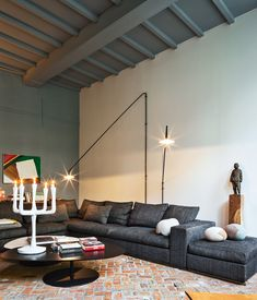 The room also contains a sofa by Flexform, cushions from textile firm Chevalier Masson, a Jens Fager candelabra, and a painting by Roger Raveel.   Photo by Tim Van de Velde.