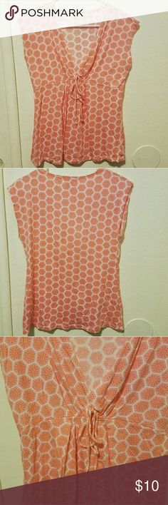 Michael Kors top This is a Michael Michael Kors shirt. Honeycomb design, cap sleeves, with a tie under the bust. Flattering deep v neckline and loose fit below bust. Small hole as shown in last picture, reflected in price. Otherwise, great condition. Peachy color, lovely for spring! MICHAEL Michael Kors Tops Tees - Short Sleeve