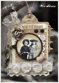 This gorgeously dimensional vintage design filled with an abundance of antique embellishments and ephemera would make a beautiful heritage scrapbook page, tag or Christmas ornament. Rolled silk roses, netting, lace, buttons and hand stitching highlight a simply matted vintage photo. To adapt into a tag or Christmas ornament, further embellish the design with an old spool of thread, keys and a twine looped top hanger ~ just stunning!