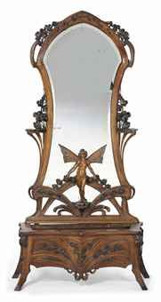 AN ART NOUVEAU CARVED WALNUT SCULPTURAL MIRROR AND JARDINIERE-STAND