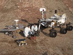 Three Generations of Rovers with Crouching Engineers : Front and center is the flight spare for the first Mars rover, Sojourner, which landed on Mars in 1997 as part of the Mars Pathfinder Project. On the left is a Mars Exploration Rover Project test rover that is a working sibling to Spirit and Opportunity, which landed on Mars in 2004. On the right is a Mars Science Laboratory test rover the size of that project's Mars rover, Curiosity, which is on course for landing on Mars in August…