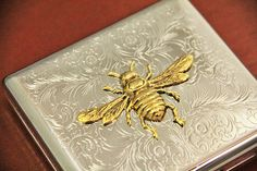Here is our nickel plated cigarette case / wallet / card holder, laid with our gorgeous 24kt antiqued gold bee charm.  The charms that we use are
