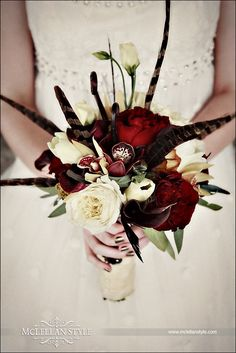 The bride's bouquet was vintage inspired yet still modern, with the incorporation of the very Victorian pheasant feathers, cream & deep ruby garden roses, deep eggplant calla lilies, fresh sage and chocolate cymbidium orchids along with fern curls, ivory lisianthus, and coffee break roses.