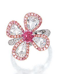 FANCY VIVID PURPLISH PINK DIAMOND, PINK DIAMOND AND DIAMOND RING Modelled as a flower, centring on a modified rectangular brilliant-cut fancy vivid purplish pink diamond weighing 0.91 carat, the petals set with four pear-shaped rose-cut diamonds surrounded by brilliant-cut pink diamonds, the shoulders pavé-set with brilliant-cut diamonds, the pink diamonds and diamonds together weighing approximately 3.40 carats, mounted in platinum.