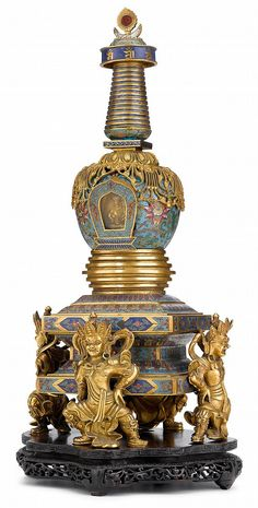 Chinese cloisonne enamel gilt bronze stupa  qianlong period  Four guardian figures supporting the square plinth of a stepped tower stupa, the sides of the stupa cast with beaded garlands and the inside set with a miniature gilt bronze figure of Buddha.  H: 17 3/4 inches
