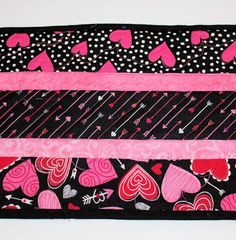 This is a sweet little quilted table runner for Valentines Day and all the month of February. The fabrics are all pink, red, white and black. Check out those cupids arrows in the center section! So many place to use it! Narrow enough for an upright piano topper. Great for a coffee table, too.  SIZE and FEATURES --- 10 wide x 39 long --- fabrics are 100% cotton of quilt shop quality --- Batting is Warm and Natural - 100% cotton --- Great for holiday decorating --- Back is a pretty pink print…