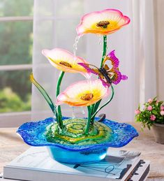 Add a decorative touch to your indoor or outdoor display with this fountain. Its cascading water feature from each lily is designed for a relaxing experience. Tabletop Fountain, Indoor Fountain, Purple Lily, Blue, Outdoor Water Features, Glass Texture, Blossom Flower, Yellow Flowers, Bright Pink
