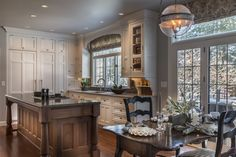 This traditional kitchen is a visual work of art amid the ordinary tasks of cooking and tidying. A myriad of display cabinets boast family keepsakes.