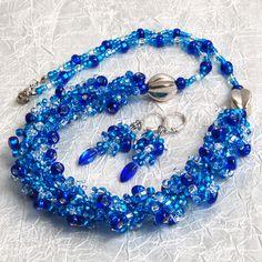 """""""Blue+harmony""""+–+souprava+Efektní+šitá+souprava+střapatého+vzhledu+v+krásných+modrých+tónech,+vyrobená+z+rokajlu+Preciosa+a+pokovených+mezičlánků.+Náušničky+jsou+drátkované+nerezovým+drátkem,+doplněné+skleněnou+slzičkou+Barevná+kombinace:+odstíny+modré,+stříbrná,+krystal+Zapínání+-+karabinka+(platina).+Obvod+náhrdelníku+55cm.+Délka+náušnic+(od+očka..."""